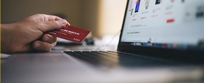 mano sujetando una tarjeta de crédito enfrente de un portátil