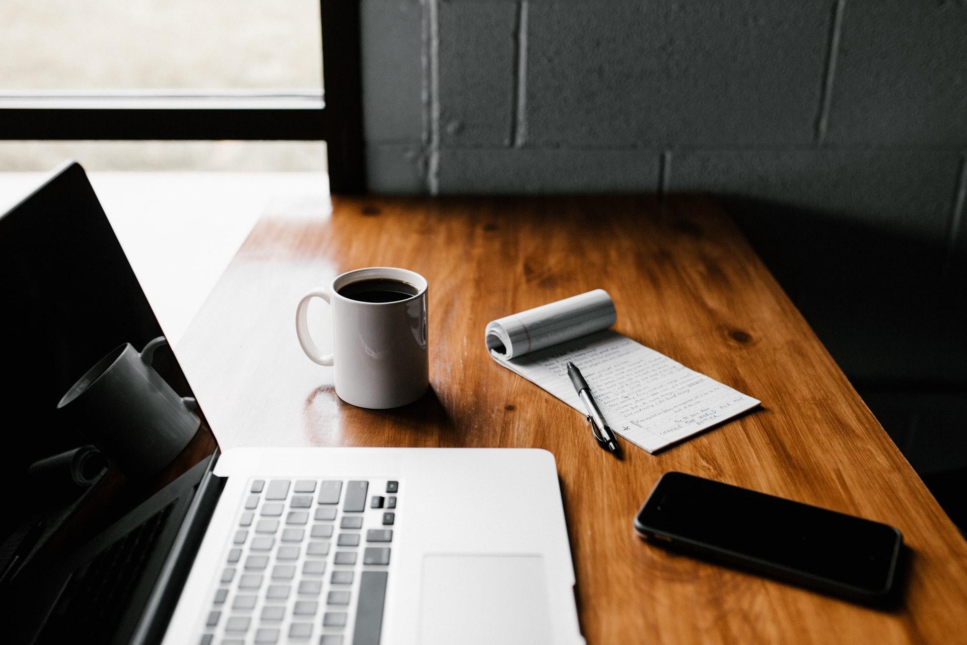 portátil encima de la mesa junto a un smartphone, taza de café y libreta