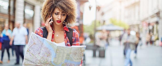mujer hablando por teléfono y mirando un mapa