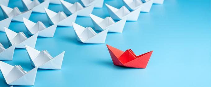 barco de papel rojo y muchos barcos blancos